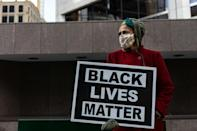 A woman holds a sign outside the Hennepin County Government Center where Derek Chauvin is on trial