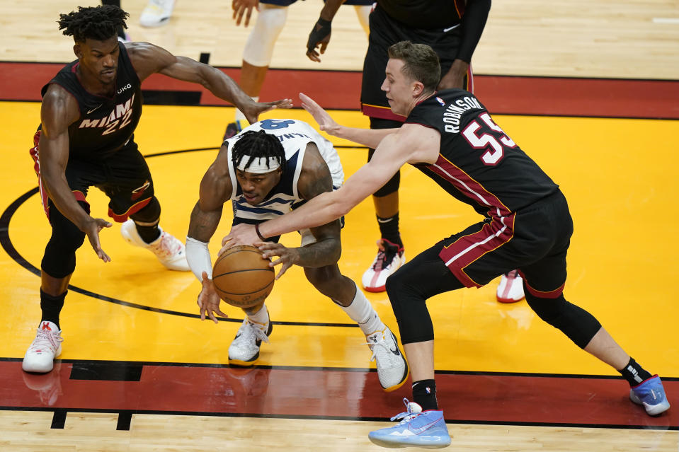Miami Heat forward Duncan Robinson (55) and forward Jimmy Butler (22) vie for a rebound with Minnesota Timberwolves forward Jarred Vanderbilt (8) during the first half of an NBA basketball game, Friday, May 7, 2021, in Miami. (AP Photo/Wilfredo Lee)