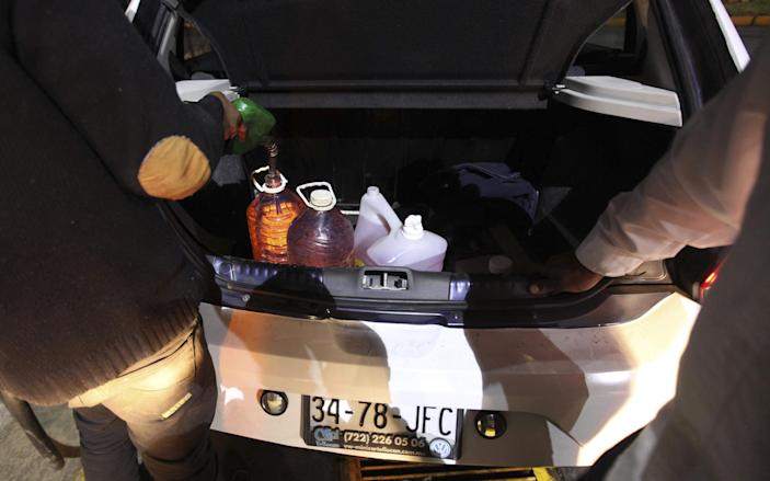 A driver fills containers in the trunk with gasoline after waiting for hours at a gas station in Valle de Bravo, Mexico, late Friday, Dec. 30, 2016. Most of the city's fill-up stations were closed on Friday night because they were out of fuel, and drivers waited up to three hours at this pump. On Jan. 1, Mexicans will start paying market prices for gasoline as part of a price deregulation, triggering gasoline shortages in many parts of the country. (AP Photo/Marco Ugarte)