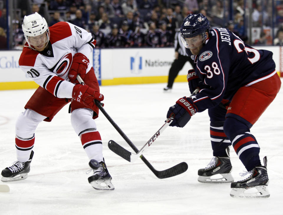 Carolina Hurricanes' Riley Nash, left, works for the puck against Columbus Blue Jackets' Boone Jenner during the first period of an NHL hockey game in Columbus, Ohio, Tuesday, Nov. 4, 2014. (AP Photo/Paul Vernon)