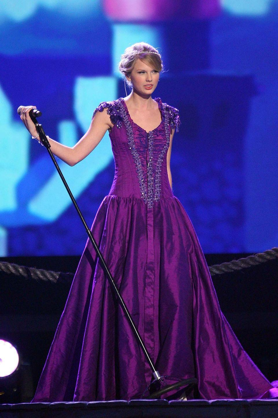 """<p>Taylor Swift wore this purple lace-up princess gown to perform her song """"Love Story"""" at the 2008 CMA Awards before <em>Tangled</em> even came out, but the whole look is still very Rapunzel to us.</p>"""
