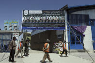 Photographs of killed students of Syed Al-Shahada School are displayed on the gate of a mosque in Dasht-e-Barchi neighborhood of Kabul, Afghanistan, Tuesday, June 1, 2021. After the collapse of the Taliban 20 years ago, Afghanistan's ethnic Hazaras began to flourish and soon advanced in various fields, including education and sports, and moved up the ladder of success. They now fear those gains will be lost to chaos and war after the final withdrawal of American and NATO troops from Afghanistan this summer. (AP Photo/Rahmat Gul)