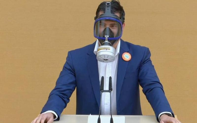An MP from the far-right AfD has worn a gas mask to protest against face coverings in Germany