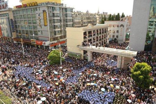 Police and protestors gather outside the local government offices in the city of Qidong, near Shanghai, on July 28. Protests against environmental degradation have increased in China, where three decades of rapid and unfettered industrial expansion have taken their toll