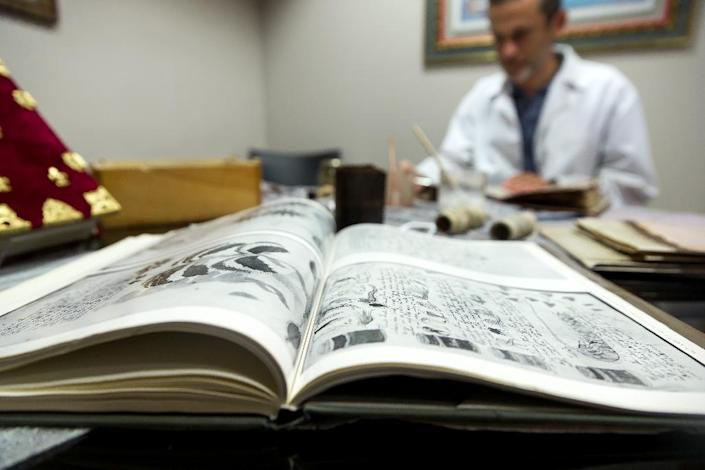 Quality control operator of the Spanish publishing outfit Siloe Luis Miguel works on cloning the illustrated codex hand-written manuscript Voynich in Burgos on August 9, 2016 (AFP Photo/Cesar Manso)