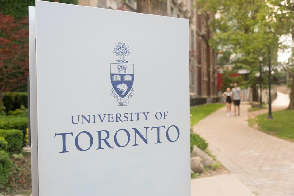 A sign for the University of Toronto in front of a footpath.