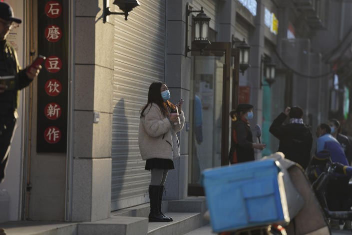 A woman wearing a mask to protect herself from the coronavirus stands along a street in Wuhan in central China's Hubei province on Thursday, Jan. 14, 2021. A global team of researchers for the World Health Organization arrived Thursday in the Chinese city where the coronavirus pandemic was first detected to conduct a politically sensitive investigation into its origins amid uncertainty about whether Beijing might try to prevent embarrassing discoveries. (AP Photo/Ng Han Guan)