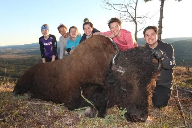 Students from Porter Creek Secondary School in Whitehorse pose with a bison they harvested during a class trip in 2019. A new report from Yukon's Child and Youth Advocate recommends more academic credit for activities outside the classroom. (Porter Creek Secondary School - image credit)