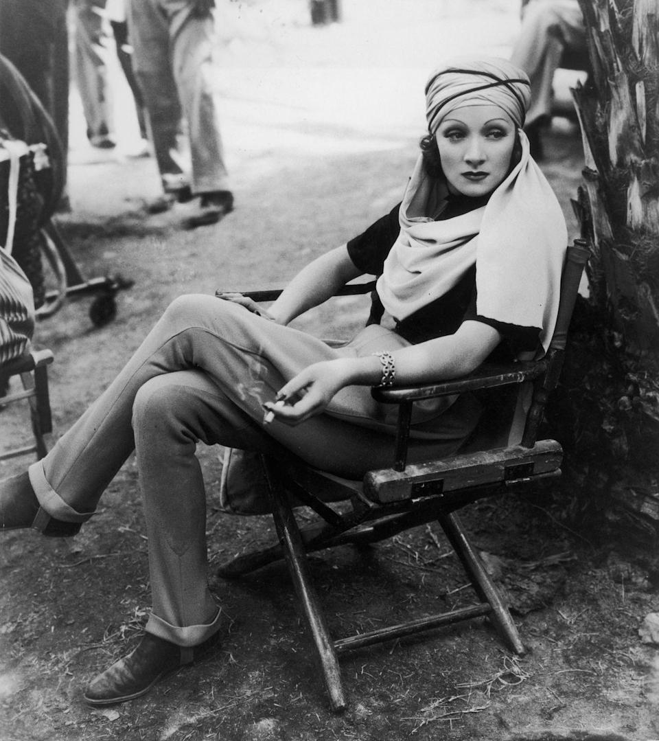 <p>Dietrich relaxes on the set of Richard Boleslawski's <em>The</em> <em>Garden of Allah</em> while smoking a cigarette and looking the part of chic starlet in rolled pants and a draped turban. <br></p>
