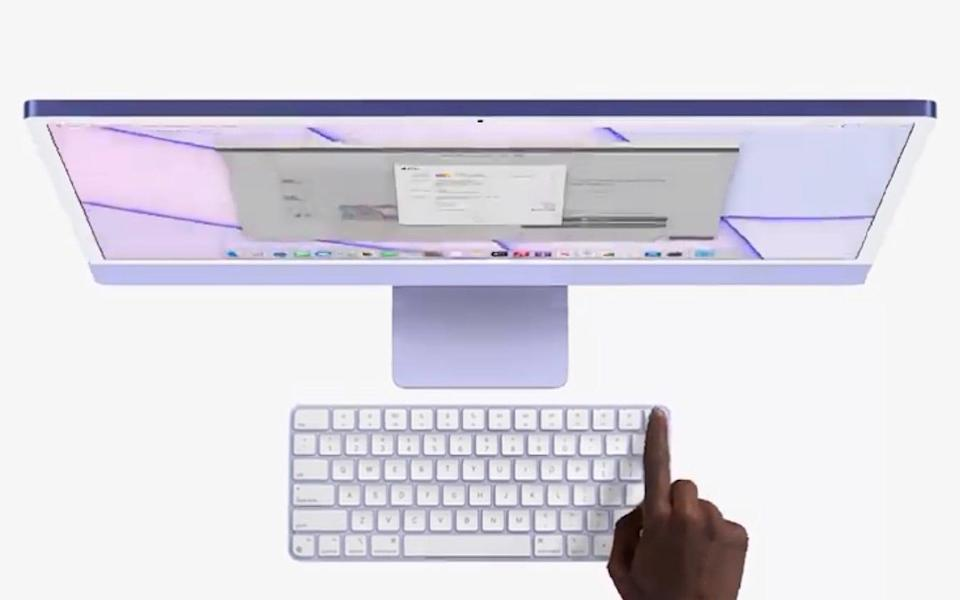 A top-down view as a finger reaches out to touch the fingerprint sensor in the top right hand corner of a lilac-purple iMac - Apple