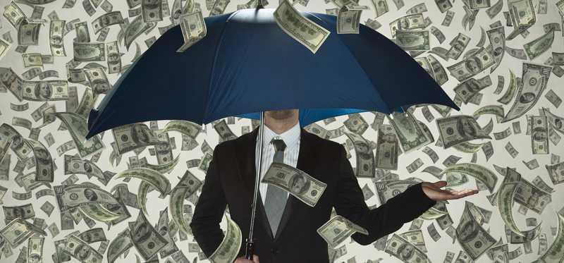 Businessman holding umbrella as money rains down.