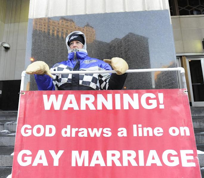 Christine Weick of Hopkins, Mich., protests outside Federal Courthouse before a trial that could overturn Michigan's ban on gay marriage in Detroit on Monday, March 3, 2014 in Detroit. Lisa Brown of Oakland County, the elected clerk of a Detroit-area county says she'll follow the orders of a judge when it comes to same-sex marriage, not Michigan's attorney general. Brown was asked about an email last fall from the attorney general's office, which warned county clerks not to issue marriage licenses to same-sex couples, even if a judge threw out the ban. Michigan voters banned gay marriage in 2004. In a lawsuit, Detroit-area nurses April DeBoer and Jayne Rowse say that violates the U.S. Constitution. (AP Photo/Detroit News, David Coates) DETROIT FREE PRESS OUT; HUFFINGTON POST OUT