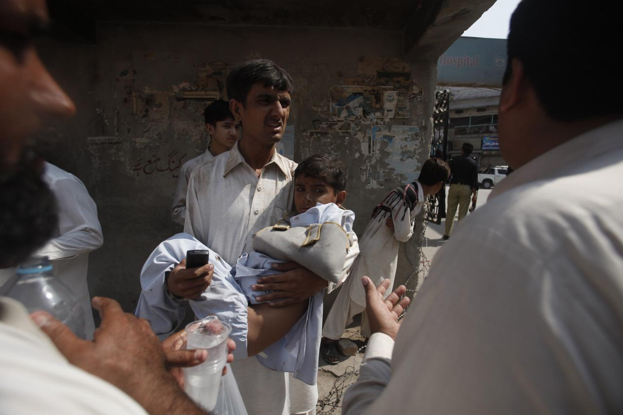 A volunteer carries a boy, who was injured in a bomb blast as he arrives at a hospital in Peshawar September 29, 2013. Twin blasts in the northwestern Pakistan city of Peshawar killed 33 people and wounded 70 on Sunday, a week after two bombings at a church in the frontier city killed scores, police and hospital authorities said. REUTERS/ Fayaz Aziz (PAKISTAN - Tags: POLITICS CIVIL UNREST CRIME LAW)
