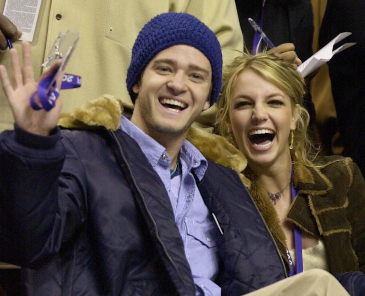 FILE - In this Feb. 10, 2002, file photo, Justin Timberlake and Britney Spears wave to the crowd prior to the start of the 2002 NBA All-Star game in Philadelphia. Timberlake told E! News on Sept. 13, 2016, that he's open to collaborating with Spears. Spears mentioned Timberlake last month in answering a question about who she would like to work with one day. (AP Photo/Chris Gardner, File)