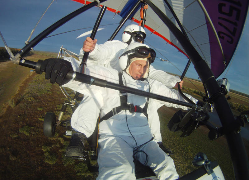 "FILE - In this Wednesday Sept. 5, 2012 file photo, Russian President Vladimir Putin, (foreground) flies in a motorized hang glider alongside a Siberian white crane, on the Yamal Peninsula, in Russia. On Thursday, Nov. 1, 2012, Interfax reported that Putin's spokesman Dmitry Peskov said the president had pulled a muscle. ""It happened before Vladivostok. He was suffering from muscle pain then"", Peskov said. Peskov told state news agency RIA Novosti this was an old injury and denied it was caused by his flight with cranes. (AP Photo/RIA-Novosti, Alexei Druzhinin, Presidential Press Service, File)"
