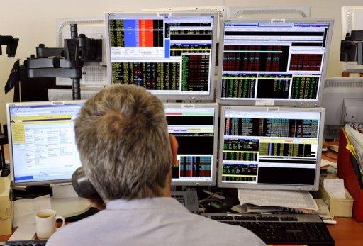 A trader looks at screens showing stock exchange share index in Paris