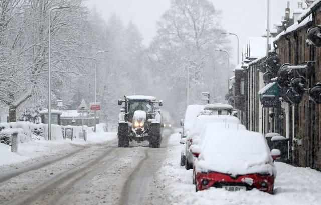 A tractor makes its way through snow in Braco, near Dunblane, in Scotland
