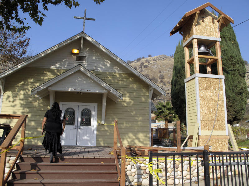 "Rhoda Hunter, tribal council secretary of the Tule River Indian Reservation, walks into Mater Dolorosa Catholic Church for Mass, Sunday, Dec. 9, 2012, at the Tule River Indian Reservation in California. The church bell, its tower being renovated, has tolled throughout the day on Sunday to honor those killed in what many believe is the worst mass murder in tribal history. Hector Celaya, 31, is a suspect in shootings in which three people died and four others, including two young girls, were wounded Saturday, Dec. 8, 2012, on the reservation in the Sierra foothills of California's Central Valley. Since 1933 the church bell has slowly tolled to alert tribal members when someone dies. ""That's our way of notifying our people that someone has passed away,"" Hunter said.  (AP Photo/Tracie Cone)"