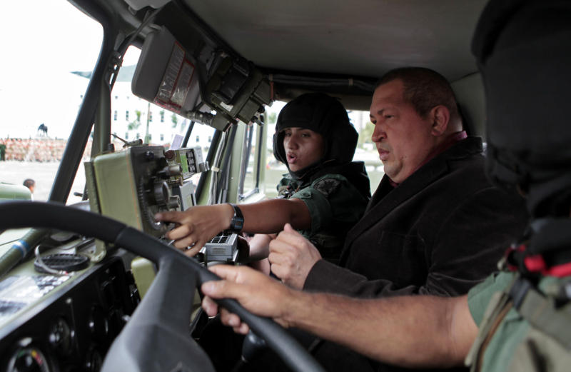In this photo released by Miraflores Press Office, Venezuela's President Hugo Chavez, right, speaks with soldiers inside a military vehicle during a military parade to commemorate the end of the year and during which some military officials were promoted at Ft. Tiuna in Caracas, Venezuela, Wednesday Dec. 28, 2011. Chavez is questioning the rash of cancer cases among Latin American leaders and asking if somehow the U.S. might have a way to induce the illness.  Chavez referred to the cancer diagnosis of Argentine President Cristina Fernandez, and noted that he and the leaders of Brazil and Paraguay have also struggled with the illness recently.  (AP Photo/Miraflores Press Office)