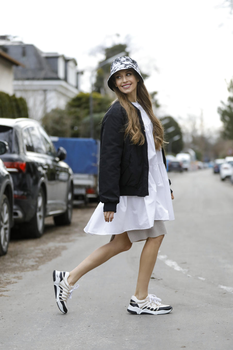 MUNICH, GERMANY - FEBRUARY 18: Influencer and TV host Cathy Hummels wearing a black and white tie dye bucket hat by Reserved, a beige skirt by Reserved, a black jacket by Yes My Love, a long white blouse by Devotion Twins and beige and black sneaker with gold stripes by Billi Bi during a street style shooting on February 18, 2021 in Munich, Germany. (Photo by Streetstyleshooters/Getty Images)