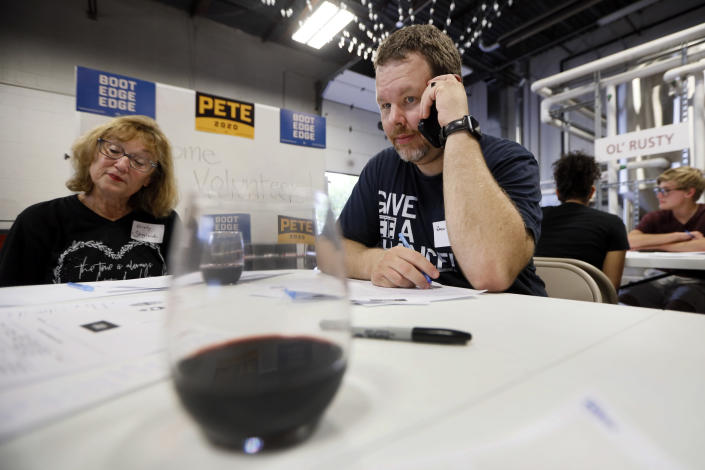 """Democratic presidential candidate Pete Buttigieg supporter Zach Norton, right, talks on his cell phone during a """"relational phone bank"""" at a local brewery, Thursday, Aug. 29, 2019, in West Des Moines, Iowa. The group worked their smartphones calling and texting friends to test their interest in the candidate. Buttigieg is well behind his better known rivals in Iowa who have spent months building a deep organizational structure in the state that marks the first test for the Democratic presidential nomination. But thanks to his campaign taking in nearly $25 million in contributions in the last quarter, money that he is using to help create an army of peer-to-peer foot soldiers, Buttigieg is rapidly trying to catch up. (AP Photo/Charlie Neibergall)"""