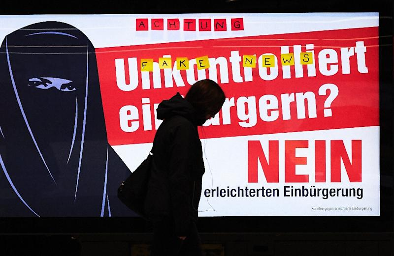 """A man walks past an electoral poster by the Committee against Facilitated Naturalization/Citizenship reading """"Uncontrolled Naturalisation? No"""" featuring a woman wearing a niqab, in a train station in Zurich, on February 7, 2017 (AFP Photo/Michael BUHOLZER)"""