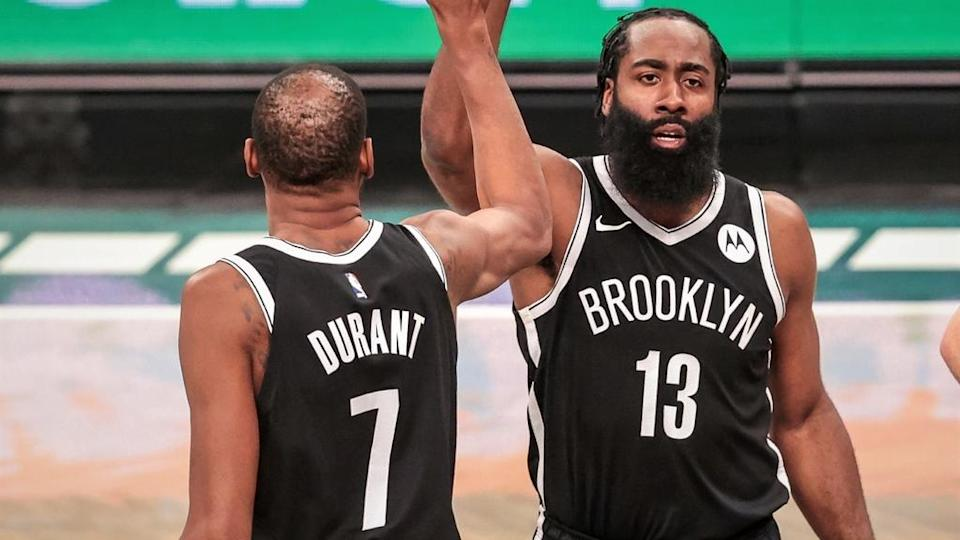 Brooklyn Nets guard James Harden slaps hands with forward Kevin Durant