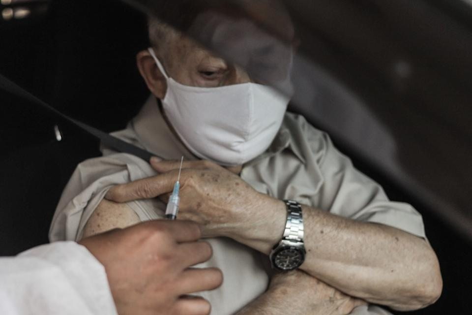 SAO PAULO, March 2, 2021 -- A health worker injects an old man with the CoronaVac vaccine developed by Chinese firm Sinovac during a drive-thru immunization at Morumbi Stadium in Sao Paulo, Brazil, on March 2, 2021. (Photo by Rahel Patrasso/Xinhua via Getty) (Xinhua/Rahel Patrasso via Getty Images)