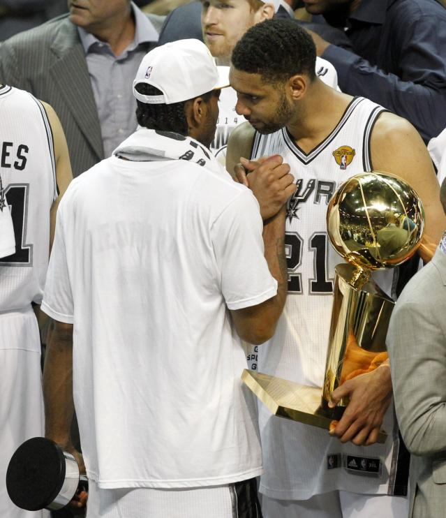 San Antonio Spurs' Tim Duncan (R) holds the Larry O'Brien trophy as he congratulates MVP Kawhi Leonard after the Spurs defeated the Miami Heat in Game 5 of their NBA Finals basketball series in San Antonio, Texas, June 15, 2014. REUTERS/Mike Stone (UNITED STATES - Tags: SPORT BASKETBALL)