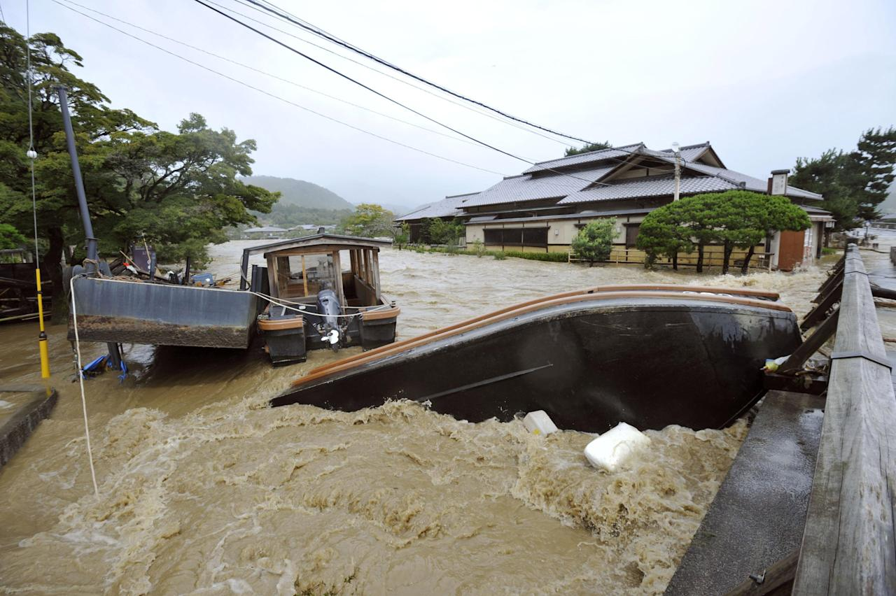 An overturned sightseeing boat is stuck by a bridge after the Katsura River was overflooded by torrential rains caused by a powerful typhoon in Kyoto, western Japan, Monday, Sept. 16, 2013. Typhoon Man-yi, one of the most powerful storms to lash Japan this season, was bearing down on Japan and went past Tokyo on Monday, leaving one dead and dumping torrential rains, damaging homes and flooding parts of the country's popular tourist destination of Kyoto, where hundreds of thousands of people were ordered to evacuate to shelters. (AP Photo/Kyodo News) JAPAN OUT, CREDIT MANDATORY