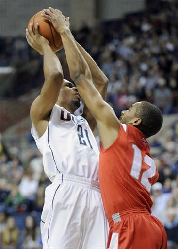 Connecticut's Omar Calhoun, left, is guarded by Stony Brook's Marcus Rouse during the first half of an NCAA college basketball game in Storrs, Conn., Sunday, Nov. 25, 2012. (AP Photo/Fred Beckham)