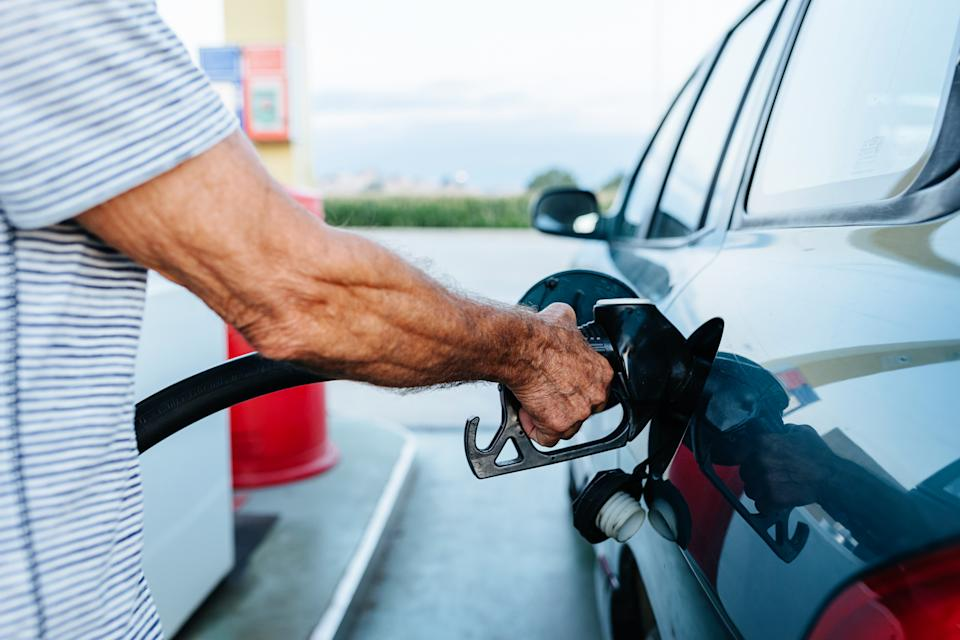Close up view of a senior man filling the tank of his car at the gas station.