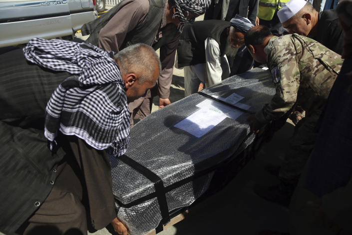 Afghan families receive the body of their relative drowned after their boat sank in Turkey's Lake Van, at the Hamid Karzai International Airport in Kabul, Afghanistan, Wednesday, July 22, 2020. The boat sank last month while ferrying dozens of migrants across a lake in eastern Turkey. (AP Photo/Rahmat Gul)