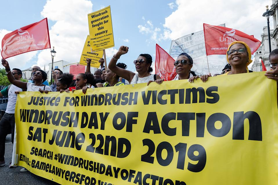 LONDON, UNITED KINGDOM - JUNE 22: A group of protesters march across Westminster Bridge to mark the first official Windrush Day with a demonstration demanding justice for members of the Windrush Generation on 22 June, 2019 in London, England. The Windrush Day of Action, taking place simultaneously in seven cities across the UK, is part of an ongoing campaign against the impact of Government's 'hostile environment' immigration policies and deportations from the UK to the Caribbean. Demonstrators call for a formal UN investigation into the Windrush scandal, an end to deportations and guarantee of full rights and compensations towards those affected by the scandal.PHOTOGRAPH BY Wiktor Szymanowicz / Barcroft Media (Photo credit should read Wiktor Szymanowicz / Barcroft Media via Getty Images)