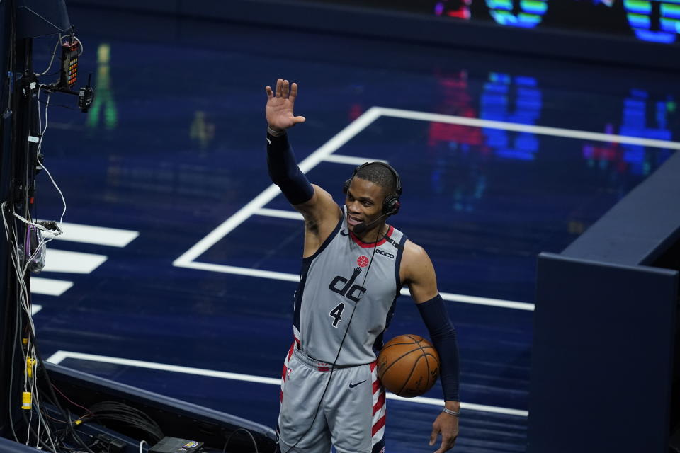 Russell Westbrook holds a game ball and waves with his other hand while wearing a headset during a postgame interview.