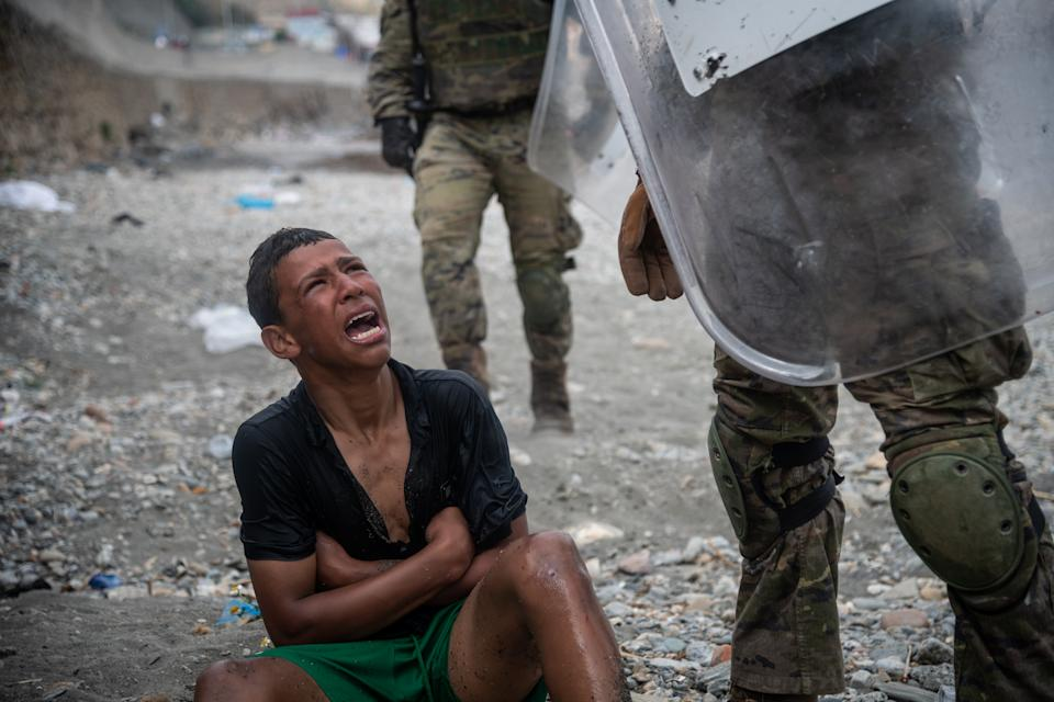 CEUTA, SPAIN - MAY 19: A migrant reacts as he talks to Spanish soldiers on the Tarajal beach after being intercepted when he was swimming across the border between Morocco and Spain on May 19, 2021 in Ceuta, Spain.  After a diplomatic conflict between Spain and Morocco, thousands of migrants who have taken advantage of the little Moroccan police activity on the border to cross it mainly by swimming, which has caused a migration crisis with the entry of more than 8000 migrants from the African country. (Photo by Joan Amengual/VIEWpress)