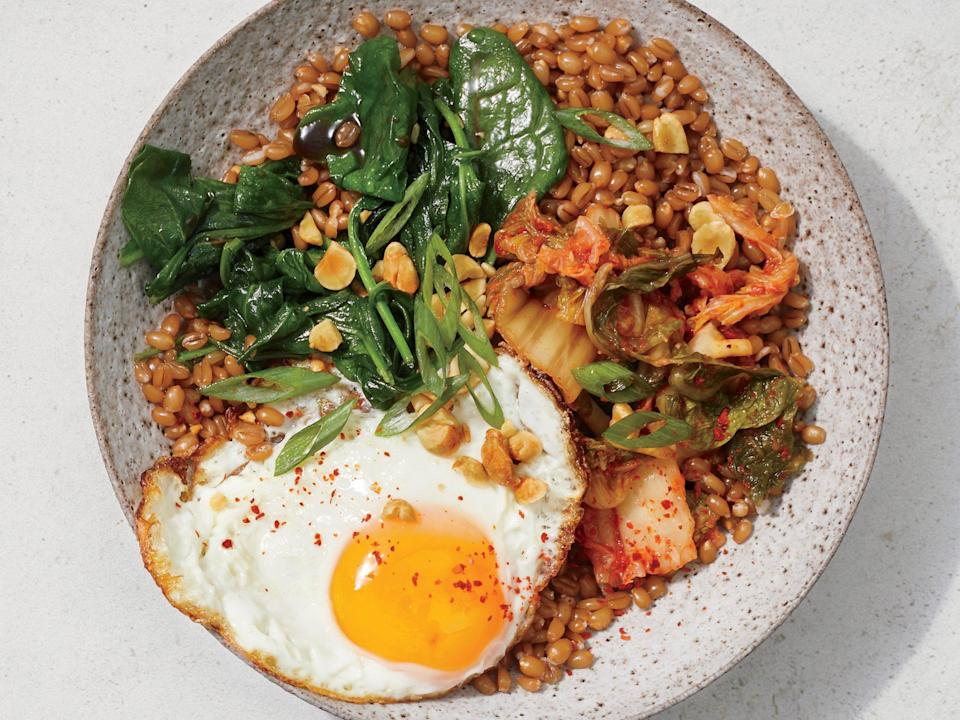 """<p>Start this hearty breakfast bowl with a batch of <a href=""""https://www.cookinglight.com/recipes/perfect-wheat-berries"""" rel=""""nofollow noopener"""" target=""""_blank"""" data-ylk=""""slk:perfect wheat berries"""" class=""""link rapid-noclick-resp"""">perfect wheat berries</a>, and then add a tangy twist and some probiotics with kimchi. Round it out with spinach, peanuts, and an egg. Sprinkle with chile flakes for extra heat. </p>"""