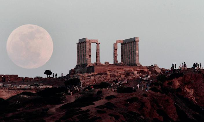 """The """"supermoon"""" rises behind the Temple of Poseidon in Cape Sounion, south east of Athens, Greece, while tourists watch, on Saturday, May 5, 2012. Saturday's event is a """"supermoon,"""" the closest and therefore the biggest and brightest full moon of the year."""