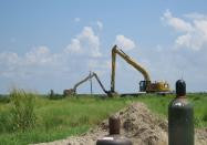 Excavators work on a Louisiana barrier island on Wednesday, July 28, 2021, creating berms to guide the placement of sand pumped from a dredge about five miles away. Contractors are at work on a $102 million Louisiana Coastal Restoration and Protection Authority project to add about 400 acres of beach, dune and marshland to Grand Terre Island. Weather permitting, they hope to finish in November. (AP Photo/Janet McConnaughey)