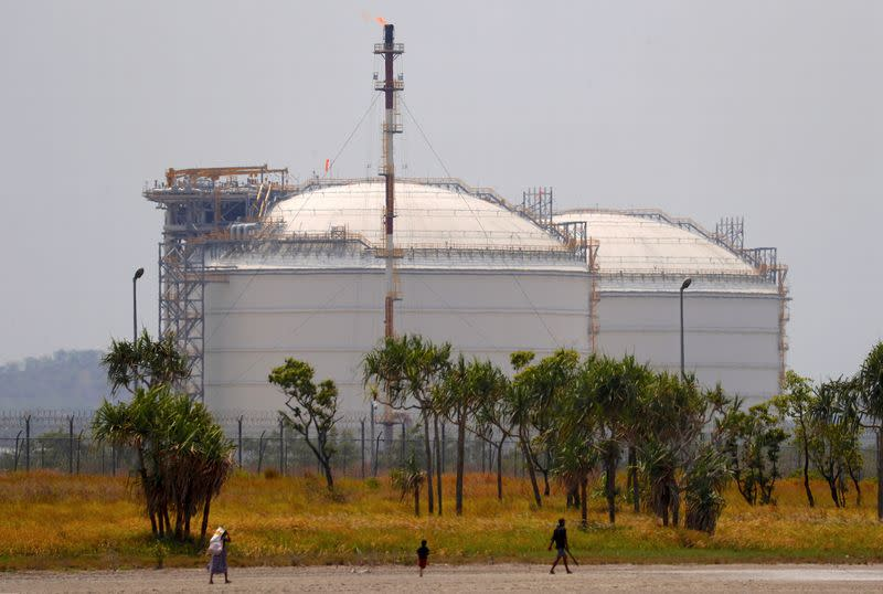 FILE PHOTO: A man holding a machete walks with his son and wife as they collect firewood in front of two Liquefied Natural Gas (LNG) storage tanks at the ExxonMobil PNG Limited operated LNG plant at Caution Bay, located on the outskirts of Port Moresby