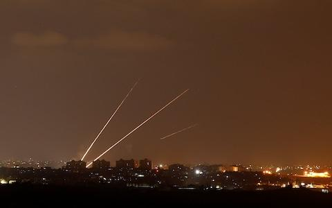 Streaks of light are pictured as rockets are launched from the northern Gaza Strip towards Israel, as seen from Sderot - Credit: Reuters