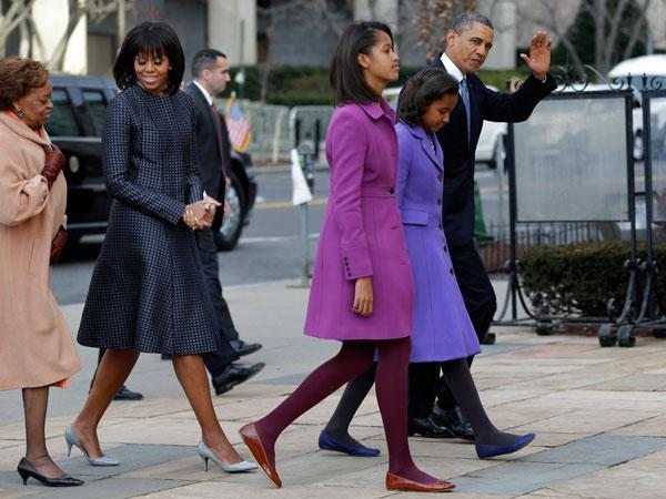 Not to be outdone by their stylish mother, Sasha and Malia Obama take a stylish turn in warm-looking coats.  Malia wears a magenta J. Crew coat while Sasha wears a light purple Kate Spade coat. The budding fashionistas also wear matching tights and complementing flats.  Maybe Malia has a future in modeling? The cute teenager has grown so much she looks almost as tall as her parents!  (AP Photo/Jacquelyn Martin)