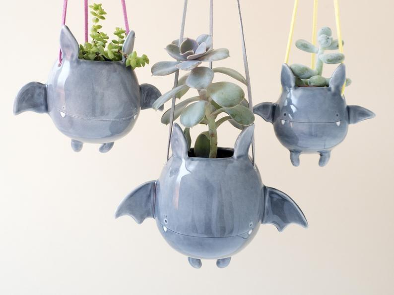 "<p>Boo! This <a href=""https://www.popsugar.com/buy/Flying-Bat-Hanging-Plant-Holder-498559?p_name=Flying%20Bat%20Hanging%20Plant%20Holder&retailer=etsy.com&pid=498559&price=49&evar1=casa%3Aus&evar9=46721965&evar98=https%3A%2F%2Fwww.popsugar.com%2Fhome%2Fphoto-gallery%2F46721965%2Fimage%2F46722060%2FFlying-Bat-Hanging-Plant-Holder&prop13=api&pdata=1"" rel=""nofollow"" data-shoppable-link=""1"" target=""_blank"" class=""ga-track"" data-ga-category=""Related"" data-ga-label=""https://www.etsy.com/listing/664809121/flying-bat-hanging-plant-holder-a-cute?ga_order=most_relevant&amp;ga_search_type=all&amp;ga_view_type=gallery&amp;ga_search_query=halloween+planter&amp;ref=sr_gallery-1-2&amp;organic_search_click=1&amp;frs=1"" data-ga-action=""In-Line Links"">Flying Bat Hanging Plant Holder</a> ($49) is so cute, it's batty.</p>"