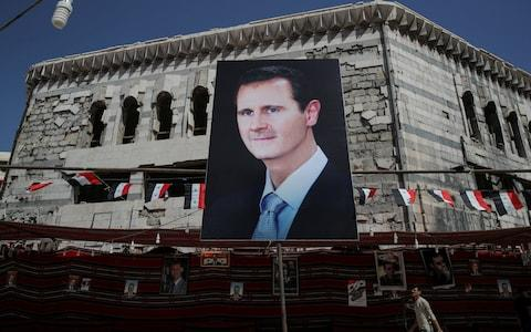 A man walks past a banner depicting Syrian president Bashar al-Assad in former opposition stronghold Douma, outside Damascus, - Credit: Reuters
