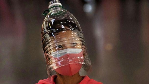 PHOTO: A girl wears a plastic bottle as a makeshift protection and a face mask while waiting to check in for a flight at Beijing Capital Airport on Jan. 30, 2020 in China. (Kevin Frayer/Getty Images)
