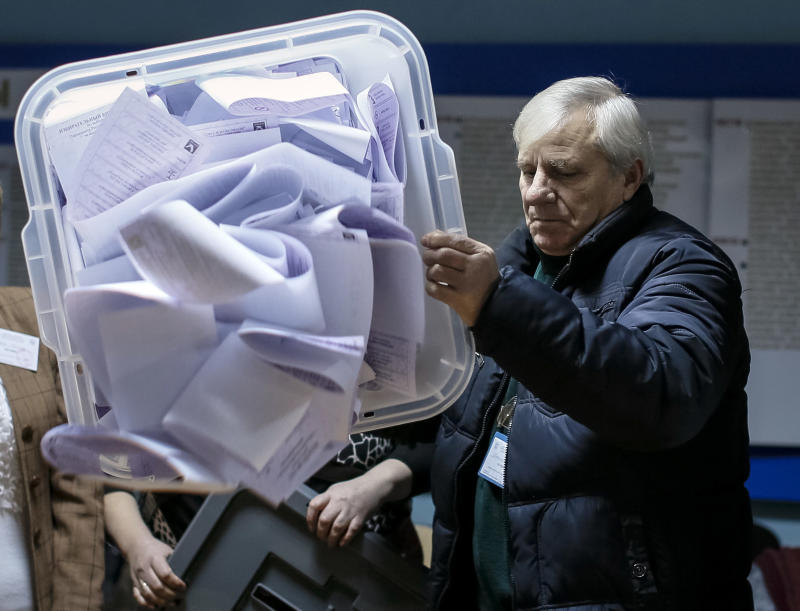 A member of a local electoral commission empties a ballot box after a parliamentary election at a polling station in Chisinau, Nov. 30, 2014. (Gleb Garanich / Reuters)