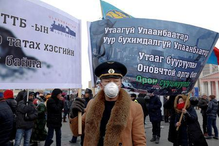 """A protester wears a face mask and holds a banner during an anti-pollution protest in central Ulaanbaatar, Mongolia January 28, 2017. The banners read ÒSmoke-free Ulaanbaatar,Ó ÒNo More Agony for Ulaanbaatar,Ó ÒThe Solution to Reducing Air Pollution is Urban Development"""". REUTERS/B. Rentsendorj"""