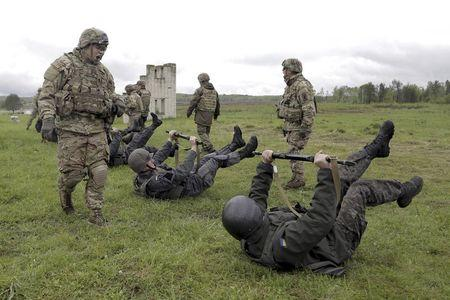 """Servicemen of the U.S. Army's 173rd Airborne Brigade Combat Team (standing) train members of the Ukrainian National Guard during a joint military exercise called """"Fearless Guardian 2015"""" at the International Peacekeeping and Security Center near the western village of Starychy, Ukraine, in this file picture taken May 7, 2015.   REUTERS/Roman Baluk/Files"""