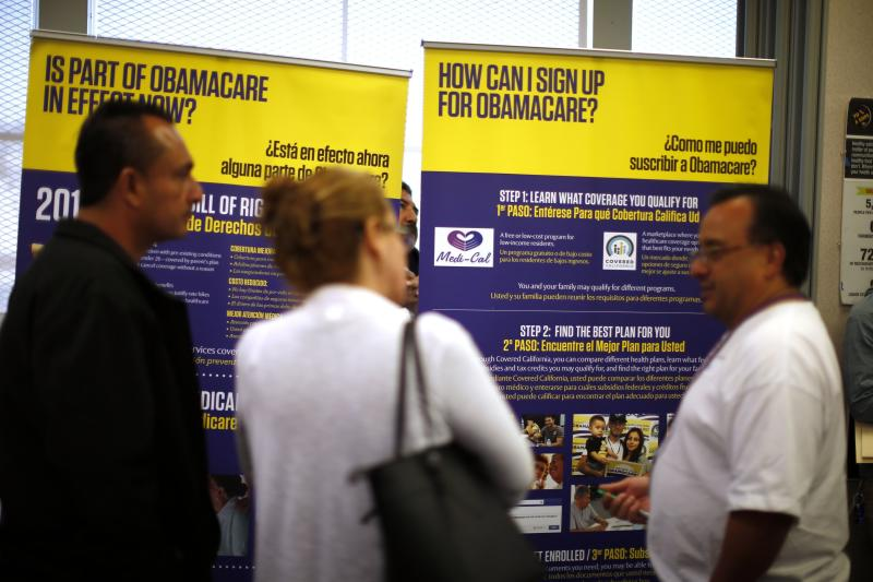 Julian Gomez (R) explains Obamacare to people at a health insurance enrolment event in Commerce, California March 31, 2014. U.S. President Barack Obama's embattled U.S. healthcare law, having survived a rollout marred by technology failures, reaches a milestone on Monday with the end of its first enrolment wave, and with the administration likely to come close to its goal of signing up 7 million people in private health insurance. More than 1 million people have signed up for Obamacare in California, according to the Los Angeles Times. REUTERS/Lucy Nicholson (UNITED STATES)