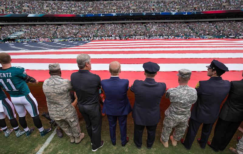 Vice President Joe Biden (blue suit),Philadelphia Eagles head coach Doug Pederson (left), and members of the military and police help hold a large American flag before a 2016 game. (USA Today Sports / Reuters)